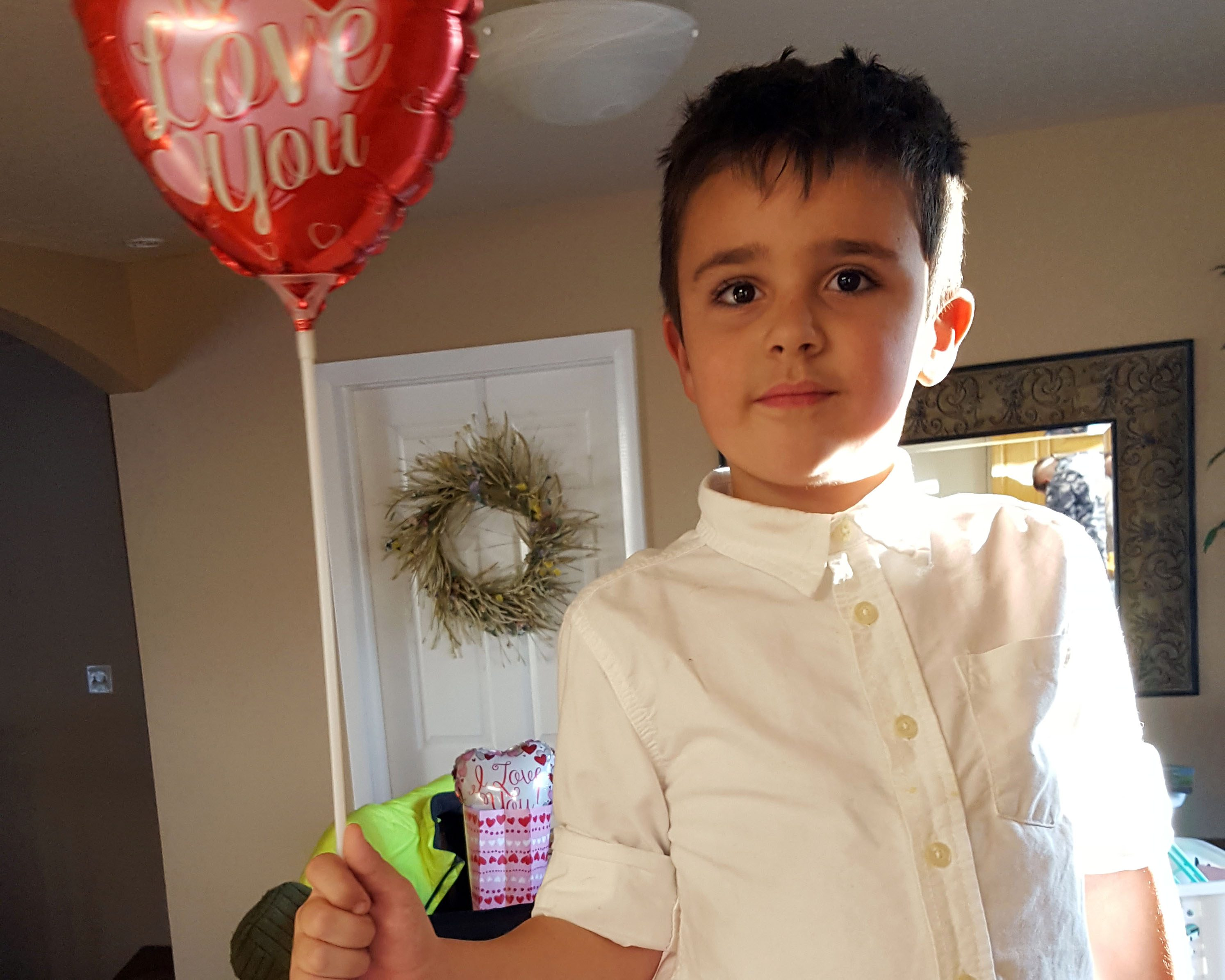 Levi holding a Valentines balloon