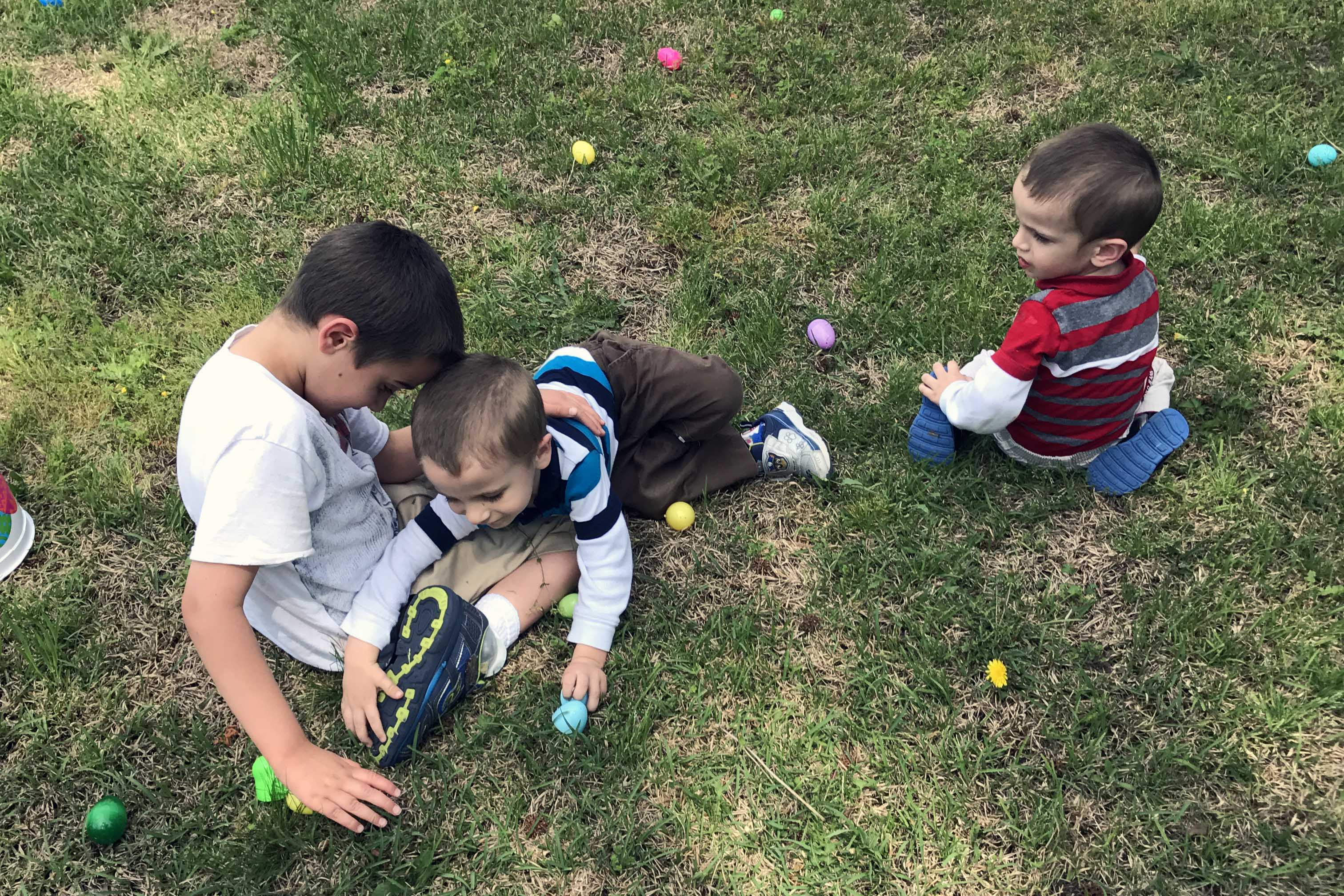 boys hunting for easter eggs on lawn