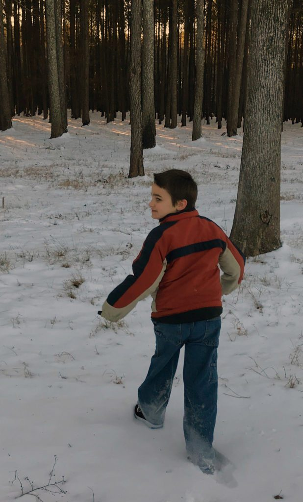 Elijah walking in snow, into the woods