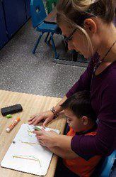 Michelle helping Caiden with writing in O.T.