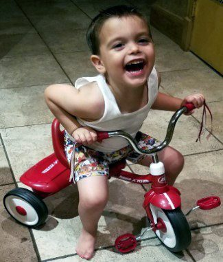 Caiden on a tricycle smiling